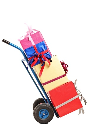 Studio shot of a hand truck with many gifts on it isolated against white background photo