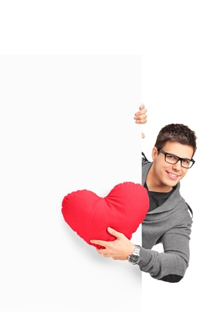 Young male holding a red heart shaped pillow and a blank banner isolated on white background photo