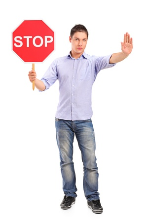 repel: Full length portrait of a man gesturing and holding a traffic sign stop isolated against white background