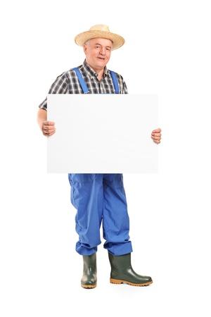 農家: 白い背景で隔離のバナーを保持している成熟した笑顔の農家の完全な長さの肖像画