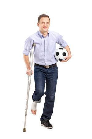fractura: Retrato de cuerpo entero de un joven herido con muletas que sostienen un bal�n de f�tbol sobre fondo blanco Foto de archivo
