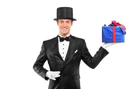 Magician holding a magic wand and a gift isolated on white background photo