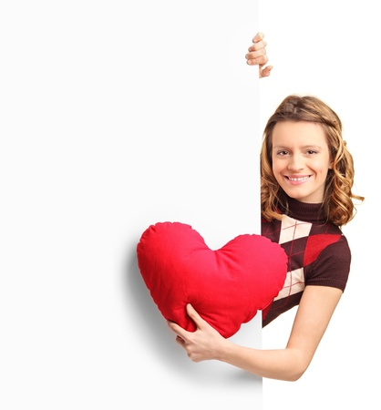 Adorable female peeking out of a banner with a red heart in her hand isolated on white background photo