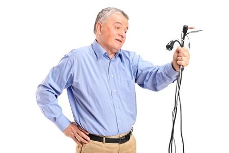 persona confundida: Confundido altos que sostienen los cables electrónicos aislados sobre fondo blanco Foto de archivo