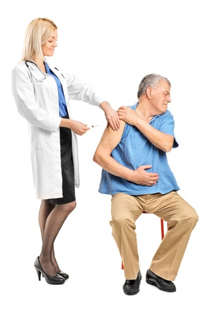 Female doctor applying a syringe to an elderly man isolated on white background