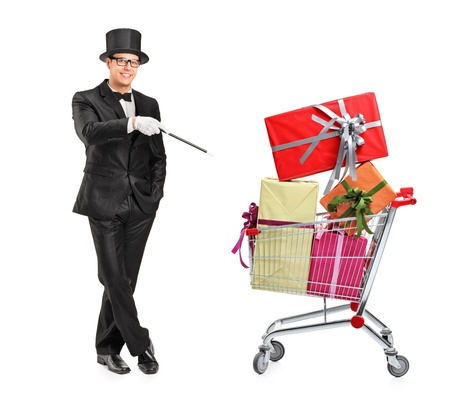 Full length portrait of a magician performing a trick on a shopping cart full of presents isolated on white background photo