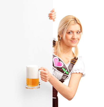 German girl holding a pint of beer behind a blank billboard, isolated on white background photo