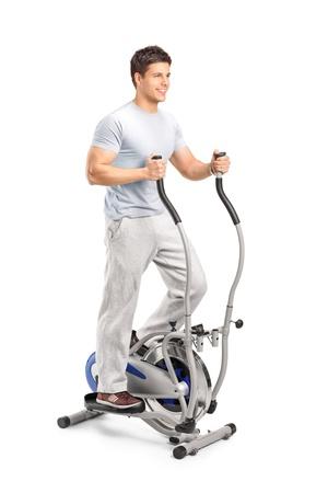 Bel homme exerce sur une machine elliptique, isolé sur blanc