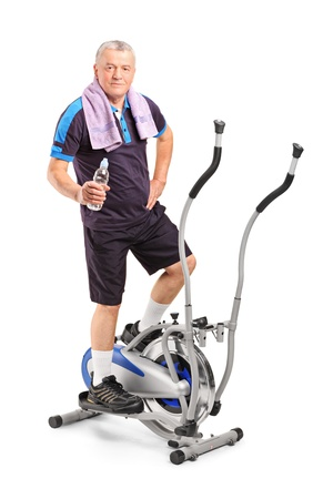 Senior man holding a water bottle and standing on a cross trainer machine isolated on white background photo