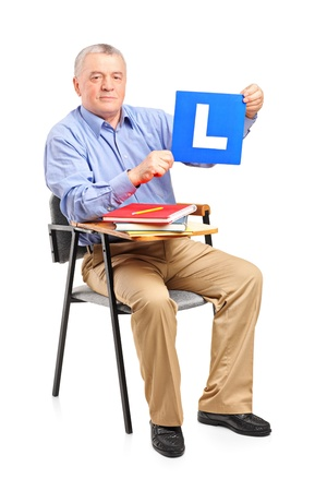 l plate: A senior man sitting on a school chair holding a L plate isolated on white background