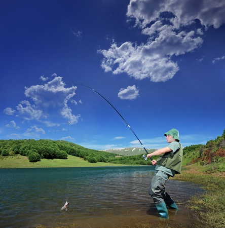 trout fishing: A view of a fisherman fishing on a Mavrovo lake, Macedonia Stock Photo