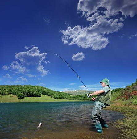 resting rod fishing: A view of a fisherman fishing on a Mavrovo lake, Macedonia Stock Photo