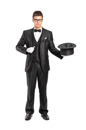 Retrato de cuerpo entero de un mago sostiene una varita mágica y sombrero de copa sobre fondo blanco