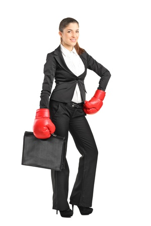 Full length portrait of a young businesswoman with boxing gloves holding a briefcase isolated on white background photo