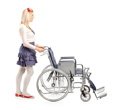 Full length portrait of a young girl pushing a wheelchair isolated on white background photo