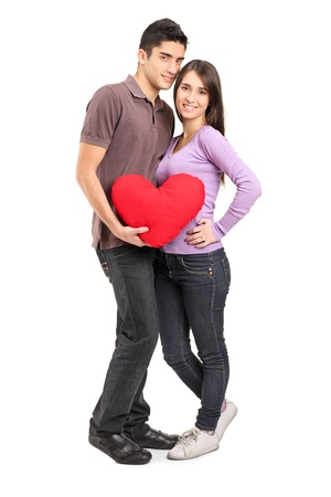 Full length portrait of a young loving couple holding a red heart shaped pillow isolated on white background Stock Photo - 12181320