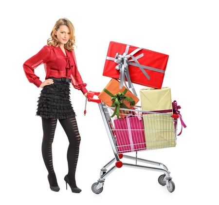 woman shopping cart: Full length portrait of an attractive woman pushing a shopping cart full of gifts isolated on white background
