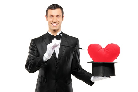 Young magician holding a magic wand and top hat with a red heart shaped pillow in it isolated on white background photo