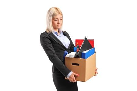 Een ontslagen zakenvrouw in een pak die een doos met persoonlijke spullen op een witte achtergrond