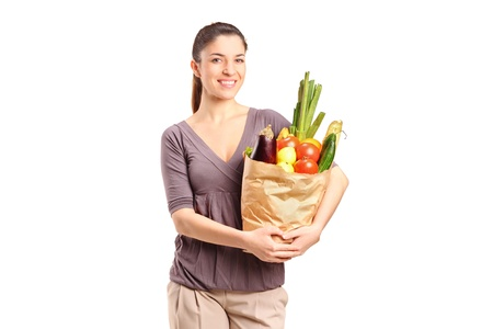 A smiling female holding a paper bag full of groceries isolated on white background photo