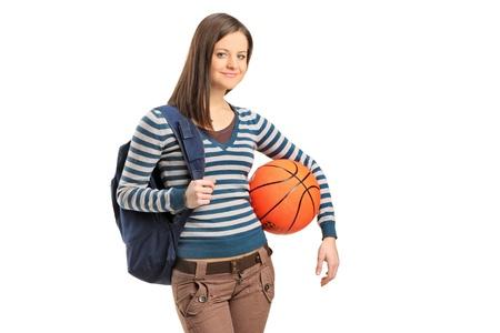 baloncesto chica: Una niña de la escuela joven que sostiene una pelota de baloncesto aislados sobre fondo blanco