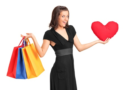 A of a smiling female holding a red heart shaped pillow and shopping bags isolated on white