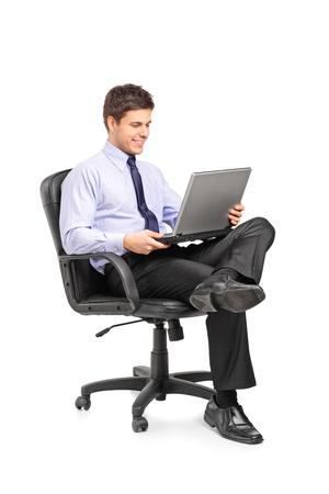 persona sentada: Hombre de negocios joven sonriente sentado en una silla de oficina y de trabajo en la computadora port�til aislados sobre fondo blanco Foto de archivo