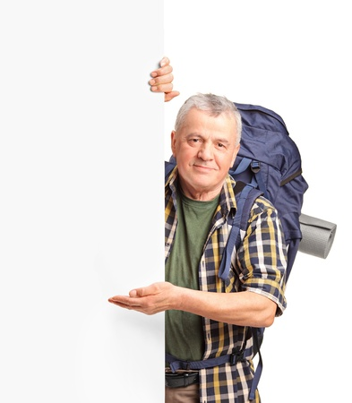 A mature backpacker gesturing on a white panel isolated on white background Stock Photo - 12633724