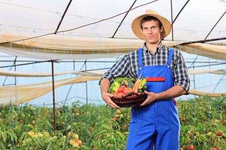 overalls: A smiling gardener holding a basket full of vegetables in a garden