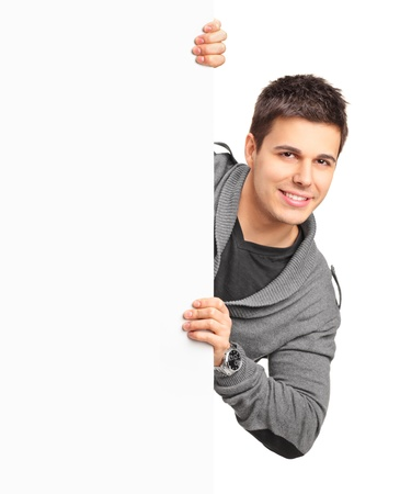 blank banner: A smiling handsome male posing behind a white panel isolated on white background