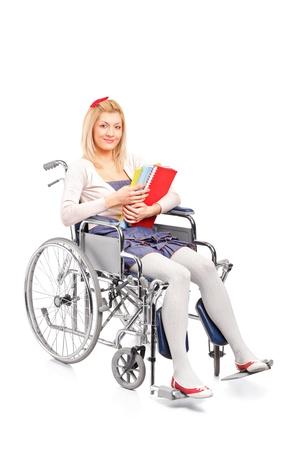 handicap people: Una chica joven y sonriente en silla de ruedas aisladas sobre fondo blanco Foto de archivo