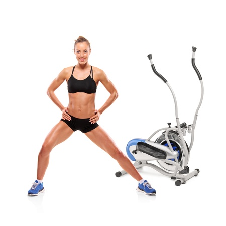 crosstrainer: An athlete woman posing in front of a cross trainer machine isolated on white background