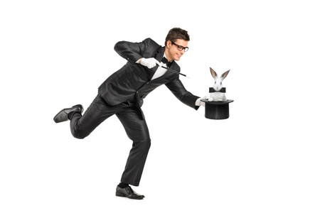 magicians: Full length portrait of a magician holding a top hat with a rabbit on it isolated on white background Stock Photo