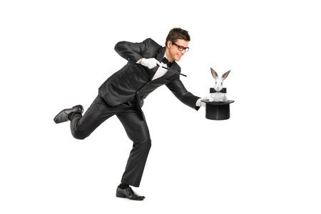 mago: Retrato de cuerpo entero de un mago que sostiene un sombrero de copa con un conejo en ella aisladas sobre fondo blanco