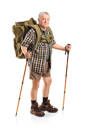 Full length portrait of a smiling mature with backpack holding hiking poles posing isolated on white background photo