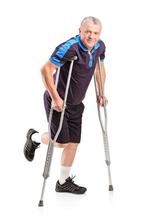 pierna rota: Retrato de cuerpo entero de un jugador senior de heridos en muletas aislados sobre fondo blanco