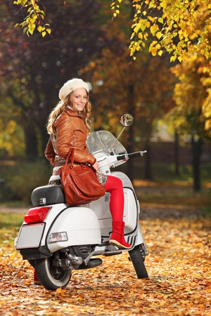 Portrait of gorgeous young woman on scooter posing in the park photo