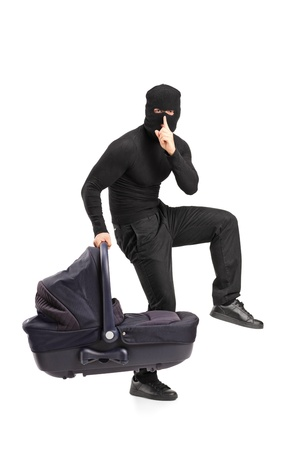 A man in robbery mask holding a carrycot with finger on the lips gesturing silence isolated on white background Stock Photo - 12633746