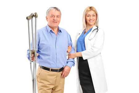 A female doctor or nurse holding a senior patient with crutches isolated on white background photo