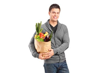 bolsa de pan: Un hombre sonriente sosteniendo una bolsa de papel llena de comestibles aisladas sobre fondo blanco