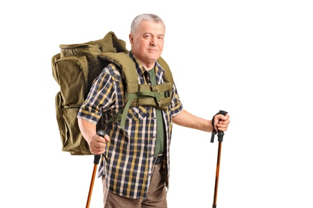 trekker: A smiling mature with backpack holding hiking poles posing isolated on white background