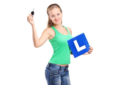 learner: A teenager holding a L plate and car key isolated on white background