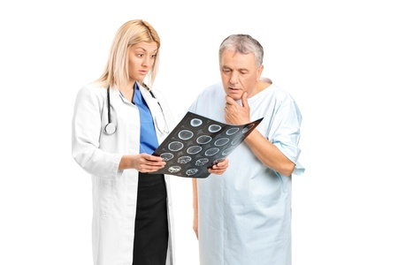 Senior man with a female doctor, looking at the results of his CT scan isolated on white background photo