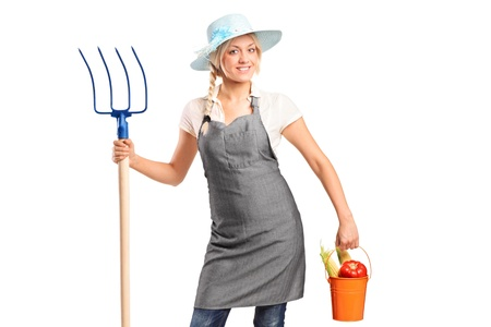 hayfork: A female farmer holding a pitchfork and bucket with vegetables isolated on white background