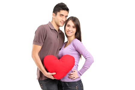 A young loving couple holding a red heart shaped pillow isolated on white background Stock Photo - 12633779