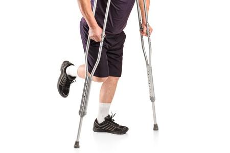 pierna rota: Un hombre herido con muletas aislados sobre fondo blanco Foto de archivo