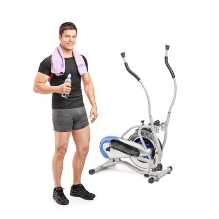 standing water: Full length portrait of an athlete standing near a cross trainer machine isolated on white background