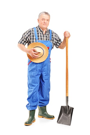 Full length portrait of a mature farmer holding a shovel isolated on white background  Stock Photo - 12633825