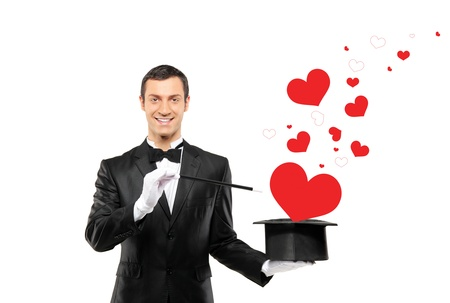 Smiling magician and a red heart shaped objects coming out of a top hat isolated on white background photo