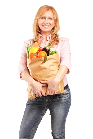 A smiling woman holding a paper bag full of groceries isolated on white background Stock Photo - 12633826